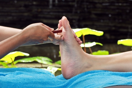 restore energy flow: foot massage by wood stick for eyes Stock Photo