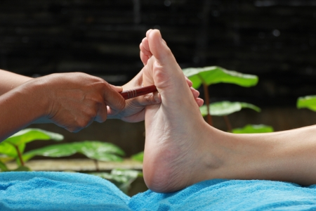 foot massage by wood stick for Thyroid gland Stock Photo