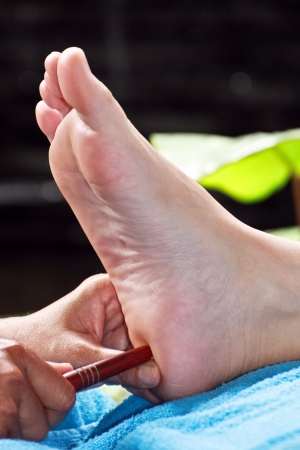 ovary: foot massage by wood stick for testis or ovary Stock Photo