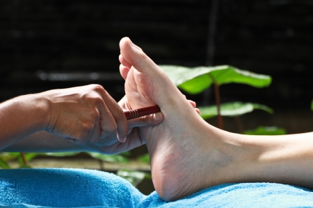 foot massage by wood stick for stomach Stock Photo - 23576032