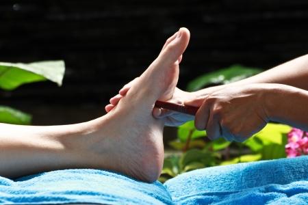 massage des pieds par le bâton de bois pour l'estomac