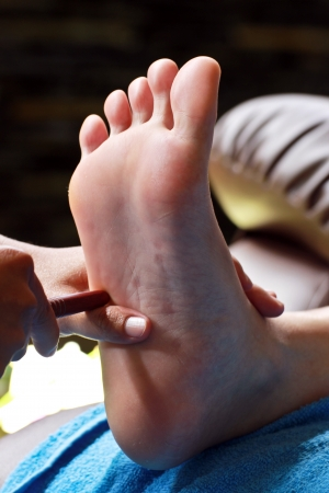 foot massage by wood stick for intestine Stock Photo - 23576034