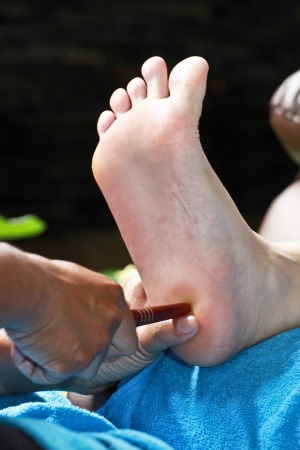 restore energy flow: foot massage by wood stick for testis or ovary Stock Photo