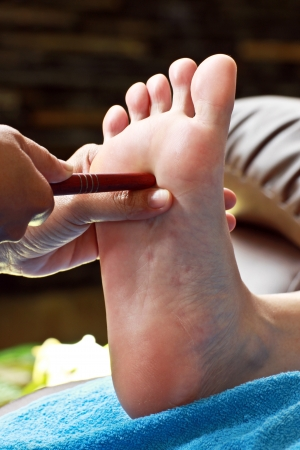 restore energy flow: foot massage by wood stick for Thyroid gland Stock Photo