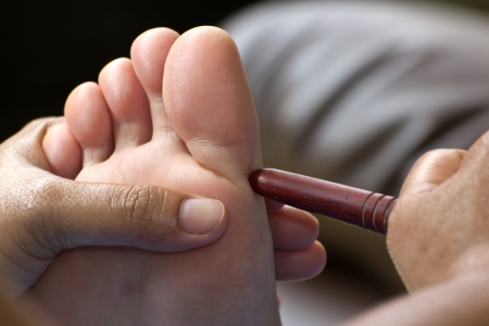 foot massage by wood stick for neck Stock Photo