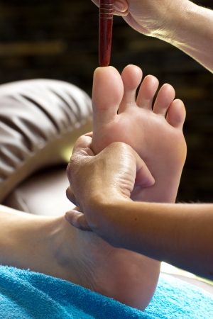 restore energy flow: foot massage by wood stick for frontal sinuses  Stock Photo