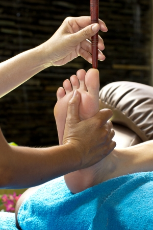 foot massage by wood stick for frontal sinuses  Banco de Imagens