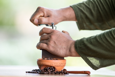 whine: Hand of barista grinding vintage coffee grinder Stock Photo