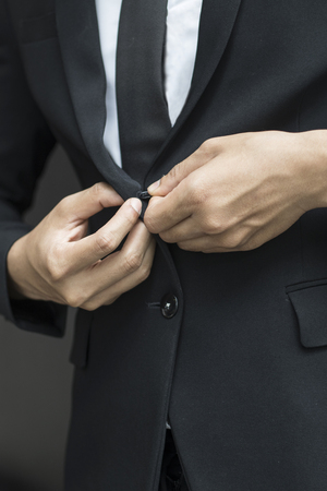 business man buttoning or unbuttoning expensive suit jacket