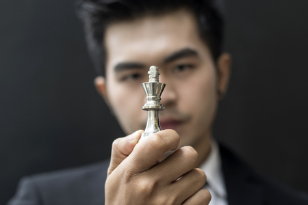 conquering adversity: concept of young business man looking at  chess on his hand and planning business plan Stock Photo