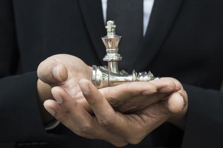 chef de l'homme d'affaires d'une entreprise prospère tenant le jeu d'échecs dans la main Banque d'images