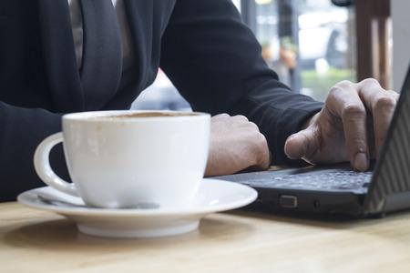 travaillant sur ordinateur portable, gros plan des mains de l'homme d'affaires