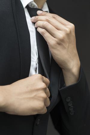jeune homme d'affaires ajustant sa cravate