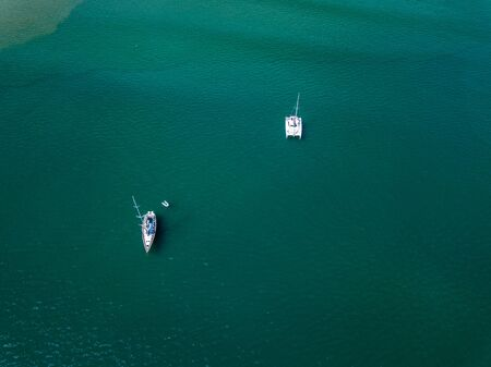 A view from a high-angle drone sees sailboats leaving anchors in a beautiful bay, clear glass-like water.
