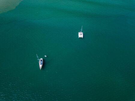 Une vue d'un drone à angle élevé voit des voiliers laisser des ancres dans une magnifique baie, une eau transparente comme du verre.