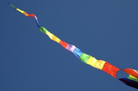 Multi-Colored Striped Kite in Blue Sky photo
