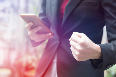 business woman holding fist while looking at cellphone