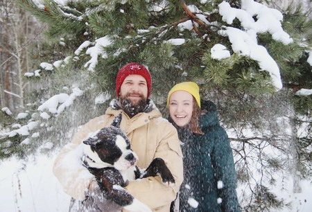 Happy couple in love having fun in the snow with his baby dog