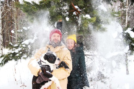 Happy couple in love having fun in the snow with his baby dog 写真素材 - 120879843