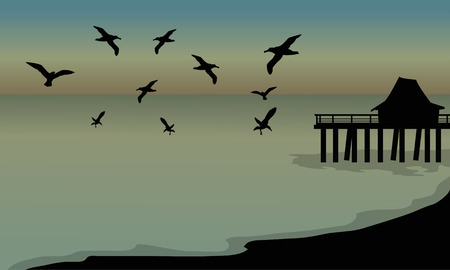 sunset beach: silhouette of huts and bird at the beach at the afternoon