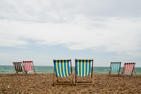 6 stripy deck chairs on a shingle beach in Brighton, Southwest England  Taken on an overcast day