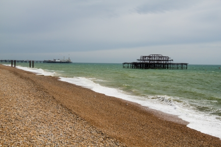 Landscape shot of the ruins of the West Pier on Brighton Beach with the shingle beach in the foreground and Palace Pier in the background