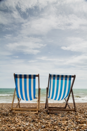 Portrait shot of 2 stripy blue and white deck chairs on a shingle beach in England looking out to sea