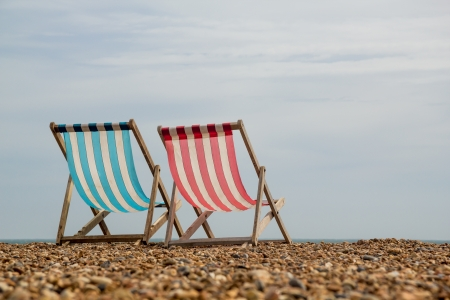 Landscape shot of 2 stripy deck chairs on a shingle beach in England looking out to sea Stock Photo