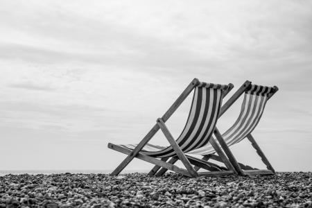 A low-angle monochrome shot of a pair of deck chairs looking out to sea