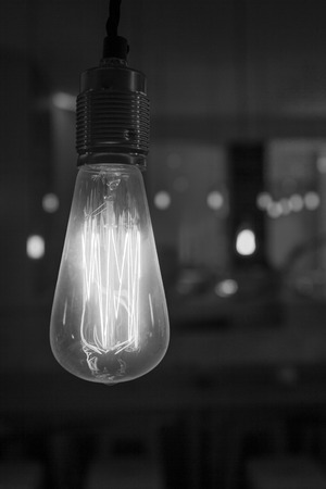 dangling: Glowing lightbulb dangling from the ceiling in black and white Stock Photo