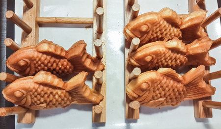 Fried fish with sweet stuffing in wooden shelf.