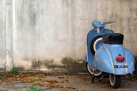 Blauwe Retro Autoped op oude muur Stockfoto