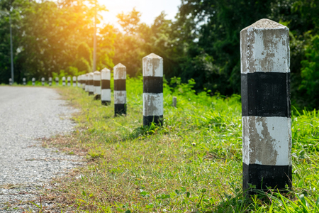 Milestones - Black and white milestones with green grass roadside, Trees roadside in background . concept for next step. Next station.Up level. Stock fotó