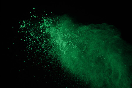 Green powder explosion on black background. Green dust explosive on dark background. Paint holi. Stop motion of green cloud