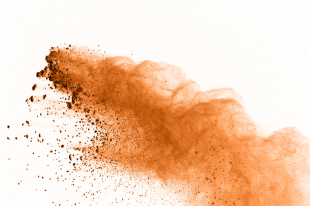 Freeze motion of brown dust explosion on white background. Stop motion of colored powder isolate background. Explosive brown powder on black background. Stock Photo