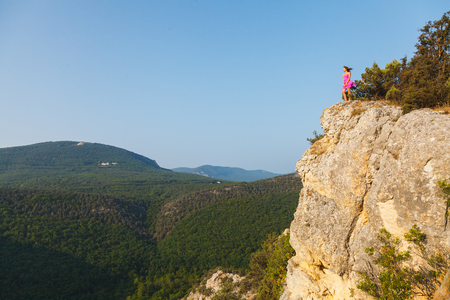 A girl in a pink dress stands on a rock in front of a big precipice