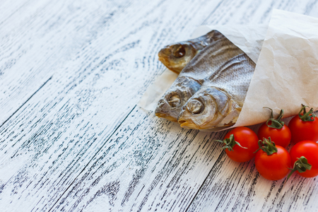 Three dried fish bream lie on a light wooden table. Fish wrapped in a paper bag. Near to lay five cherry tomatoes.