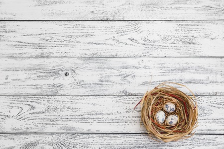 Easter eggs lie in a nest on the background of a light wooden table in vintage style. Quail eggs.