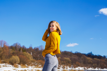 Girl in a yellow sweater posing against the blue sky and winter forest. She turned her back, see a smiling face. Imagens