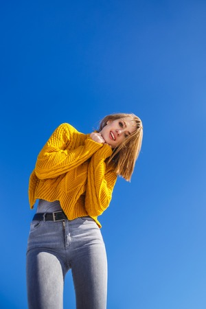 Portrait of an emotional girl in a yellow sweater and short hair. Blue sky background can be used for text. Imagens