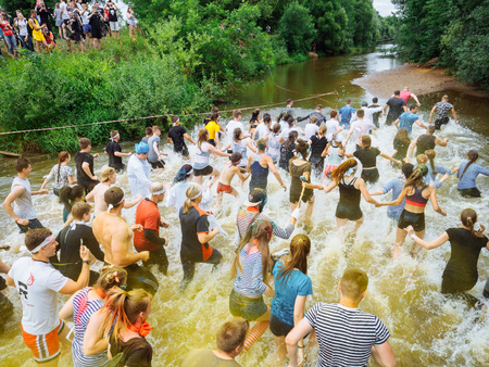 RUSSIA, Bryansk - June 30, 2018: Obstacle Race. Athletes in suits at the start of running on the river. Editorial