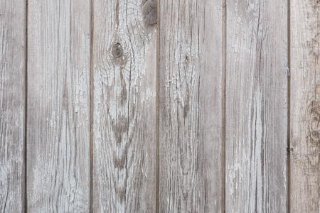 La textura de la vieja valla gris en mal estado y restos de pintura blanca. Foto de archivo