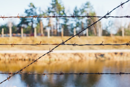 Dangerous area fenced with barbed wire fence. Banque d'images - 121043377