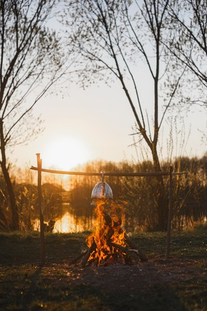 Kettle over the fire on the lake in the evening.