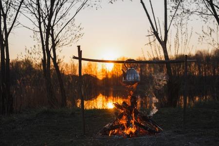 Teapot on the fire prepares tea. Orange sunset. Standard-Bild - 124447093