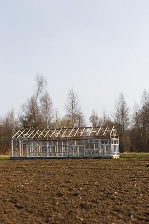 Gewächshaus aus den Fenstern im Garten im zeitigen Frühjahr. Standard-Bild