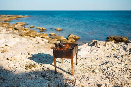 Burning BBQ on a stone sea beach. Stock Photo