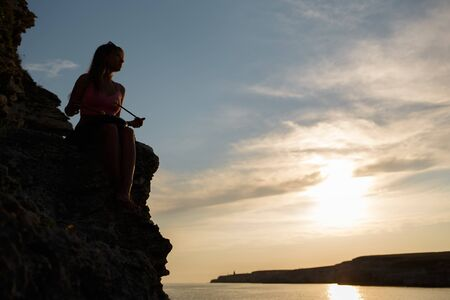 Girl playing a glucophone on a rocky seashore.
