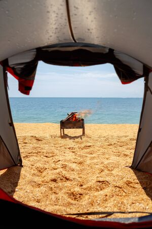 View from the tent to the sea. In the background is a burning barbecue.