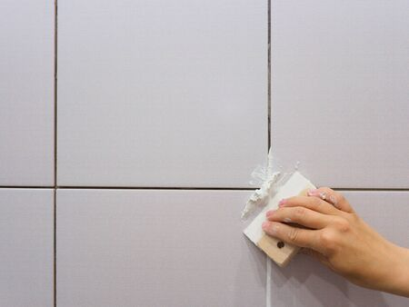 Grouting between tiles in the bathroom. Female hand holds a spatula. Repairs.